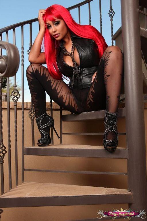 Priya Rai in a red wig and black body stocking