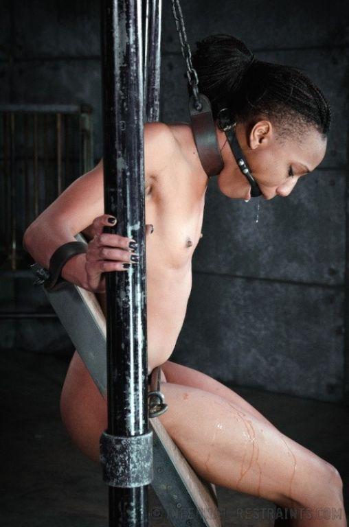 Nikki Darling ebony is bound in wooden stocks her
