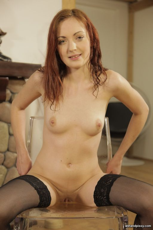 Sexy redhead toys her piss soaked pussy with a dil