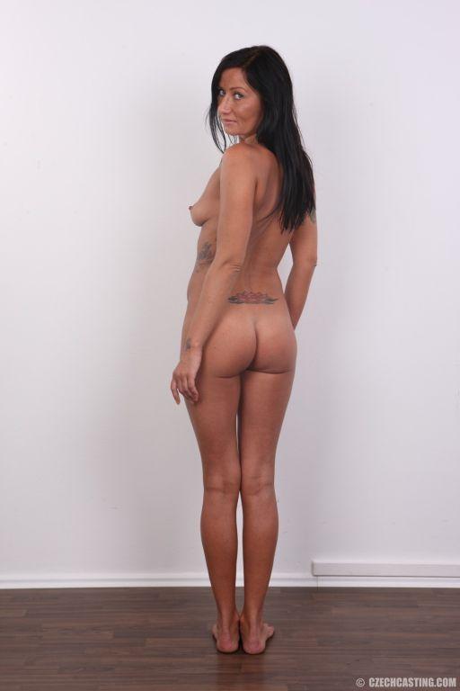 Tattooed brunette poses naked