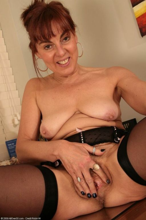 Mature secretary in black stockings strips at offi