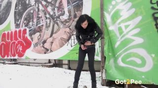 Pretty dark haired girl melts snow as she pees