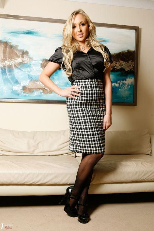 Danni King in silk shirt plaid skirt and black sto