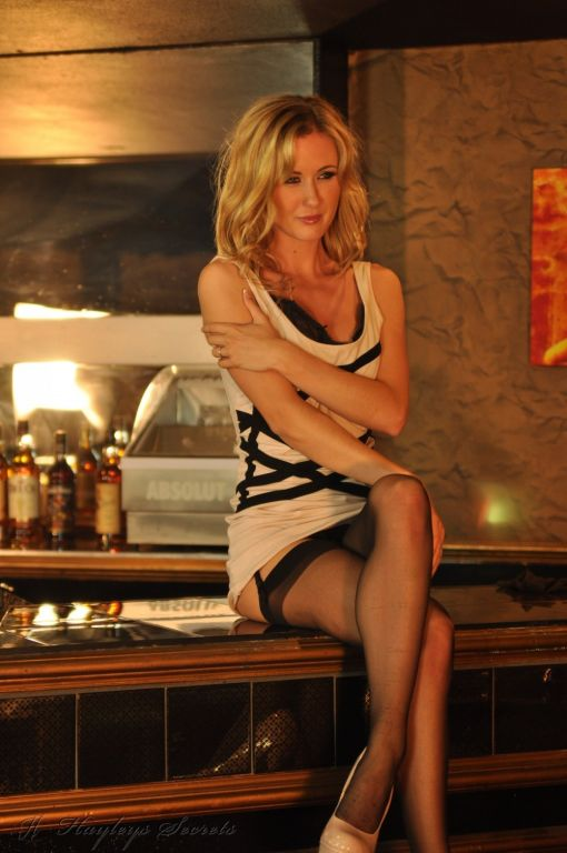 Sam Tye posing in the bar in her black lingerie