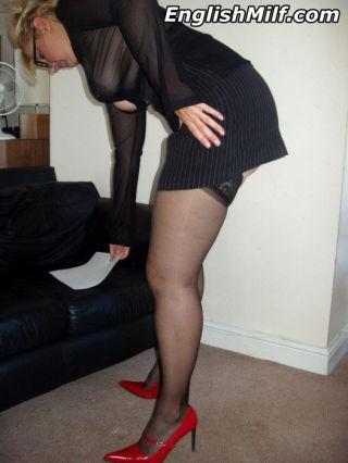 Office slut Daniella English posing in red heels