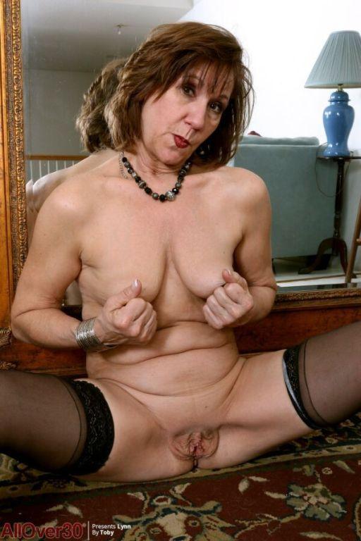 Elle Denay in black stockings poses before a mirro