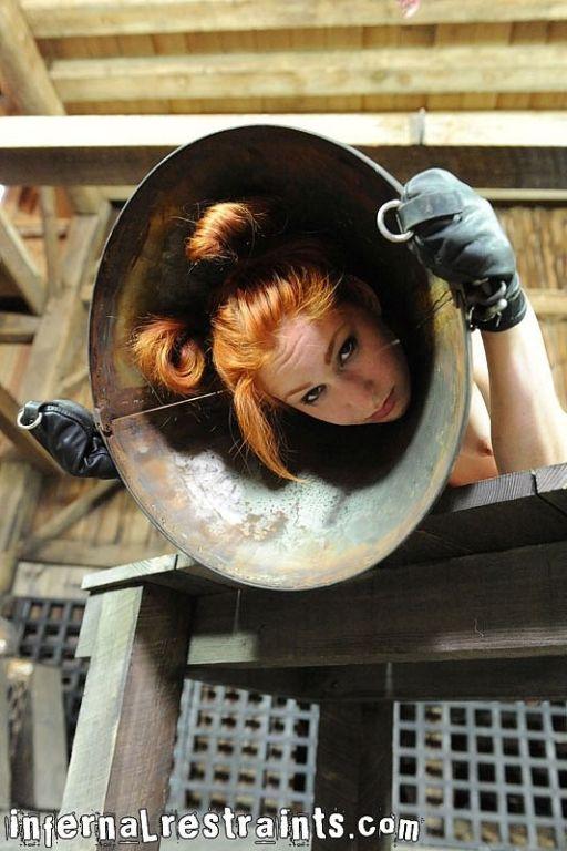 Calico Slave kinky redhead is bound with metal hoo